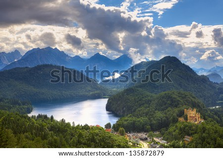 Aerial view on medieval castle on the hill near alpine lake among mountains under cloudy sky in Bavaria, Germany.