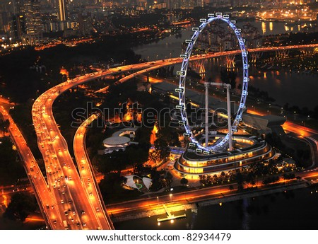 Aerial view on Singapore Flyer from Marina Bay Sands resort at night - stock photo