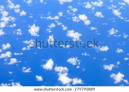 Aerial view on some clouds in the sky above the ocean seen from above  - stock photo
