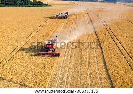 Aerial view on the combines and tractors working on the large wheat field - stock photo