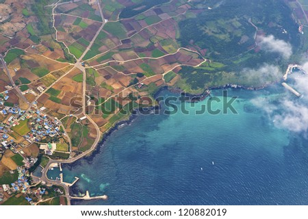 aerial view on the cultivated land and on the suburbs urban along marine coast - stock photo