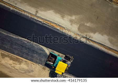 Aerial view on the road rollers working on the new road construction site - stock photo