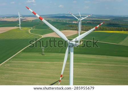 Aerial view on the windmills on the green field - stock photo