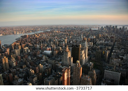 Aerial view over east lower Manhattan from Empire State building top, New York at sunset - stock photo
