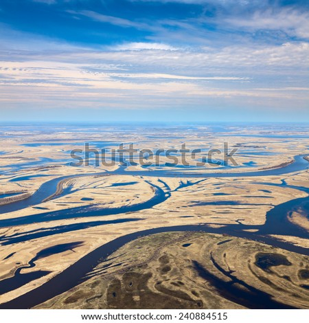 Aerial view over flood-land beside great river during spring. Great plain is divided into many parts by a lot of number of rivers and channels. Water meadows are covered by yellow last year's grass. - stock photo