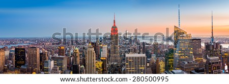 Aerial view over New York City at sunset. The Empire State Building is colored in red to honor the New York City Fire Department (FDNY) - stock photo