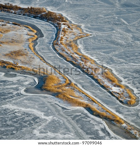 aerial view over small river in wintertime - stock photo
