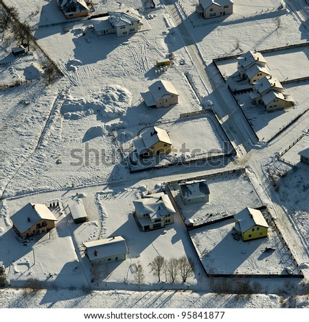 aerial view over small village in wintertime - stock photo
