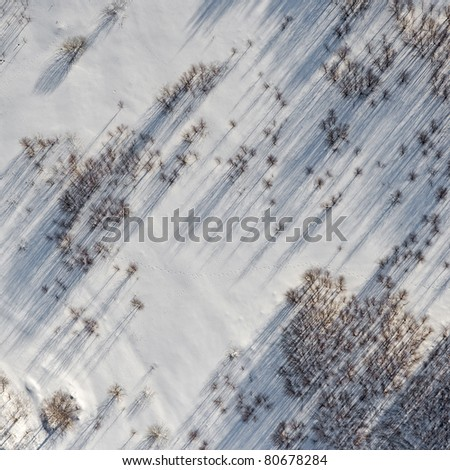 Aerial view over snowy field - stock photo