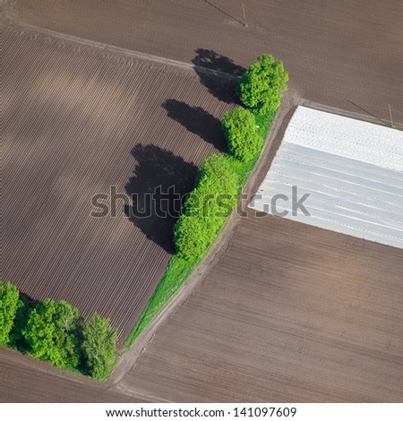 Aerial view over the agricultural fields and country road in springtime - stock photo