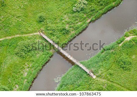 aerial view over the bridge on the small river - stock photo