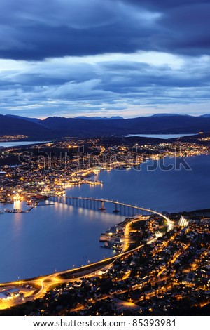 Aerial view over Tromso Bridge - linking the mainland (Tromsdalen) with the city central island (Tromsøya) - stock photo