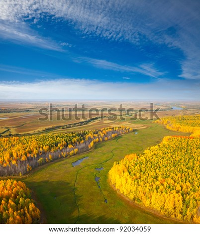 Aerial view overview a autumn forest under clouds in the time of sunset.