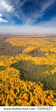 Aerial view overview a autumn forest under clouds in the time of sunset. - stock photo