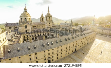 Aerial view Royal Monastery of San Lorenzo de El Escorial near Madrid, Spain against sun with strong sunbeam flare light / STUNNING VIDEO AVAILABLE (4K UHD Quality) on my footage gallery. - stock photo