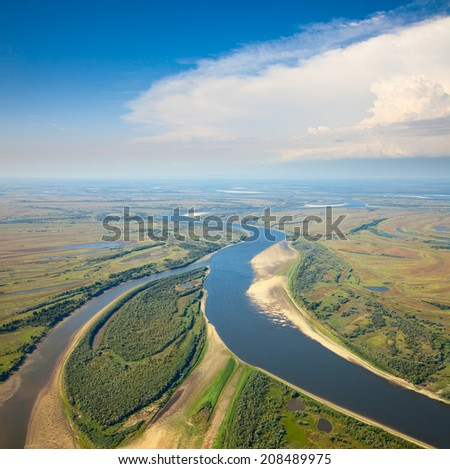 Aerial view the plain river under white clouds during summer day. - stock photo