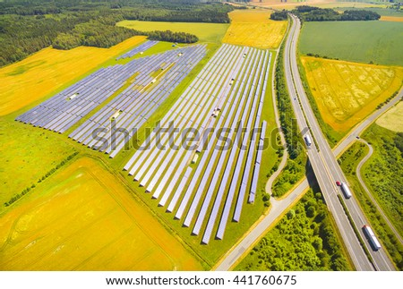 Aerial view to solar power plant near highway with traffic. Industrial background on renewable resources theme. - stock photo