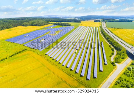 Aerial view to solar power plant near highway with traffic. Industrial background on renewable resources theme.