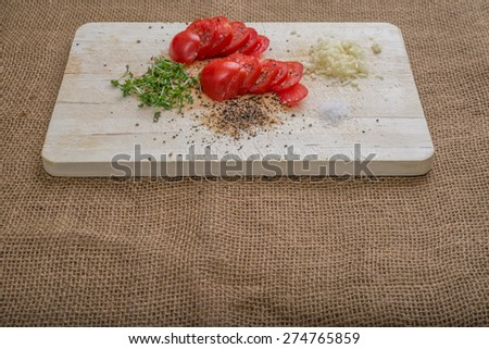 Aerial view tomatoes cress garlic salt pepper on burlap background  Vegan salad preparation for healthy meal, clean eating with organic food for detox diet on wooden cutting board - stock photo