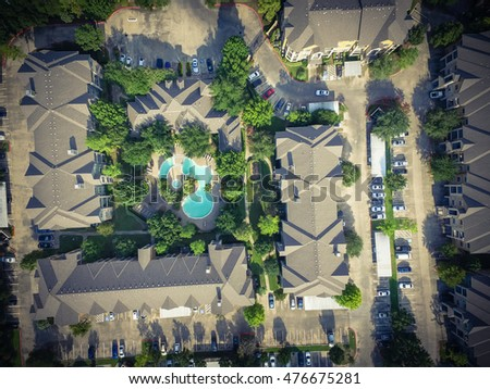 Aerial view typical multi-level apartment building complex with swimming pool, surrounded green garden and rows of cars in parking lots in Houston, Texas, US. Residential recreation concept. Vintage.