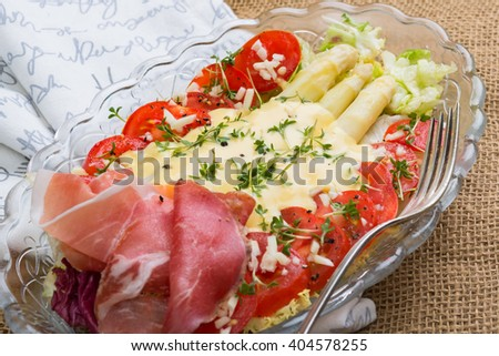 Aerial view white asparagus tomatoes lettuce salad on burlap background.  Vegan salad for healthy meal, clean eating with organic food, image for detox diet low carb low fat on glass plate