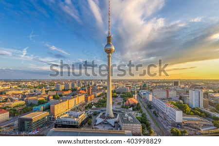 Aerial wide angle view of Berlin skyline with famous TV tower at Alexanderplatz and dramatic clouds in beautiful golden evening light at sunset in summer, Germany - stock photo