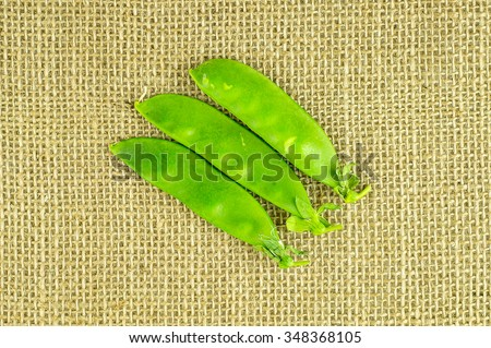 Aeriel shot of fresh green snow pea pods on hessian - stock photo