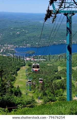 Aeriial View of Peoples using the chairlift to ascend and descend the Tremblant mountain, with background The Village of Tremblant and the Laurentian Mountains. - stock photo