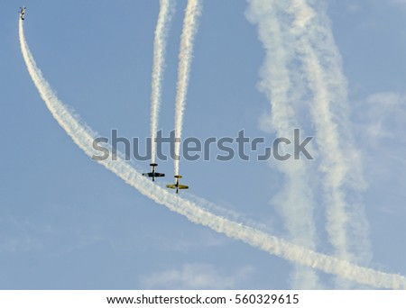 Aerobatic pilots with her colored airplanes training in the blue sky, trace colored smoke.