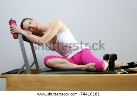 aerobic gym pilates woman rest holding water bottle in reformer bed - stock photo