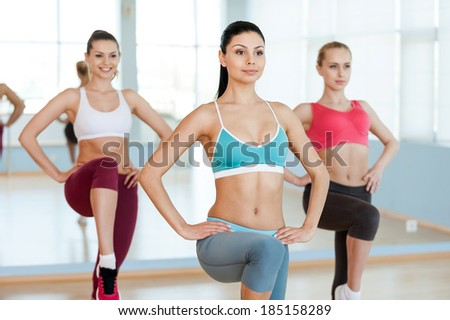 Aerobics class. Three beautiful young women in sports clothing exercising together and smiling - stock photo
