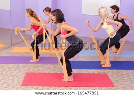 Aerobics HOT pilates group with rubber bands in a row at fitness gym  - stock photo