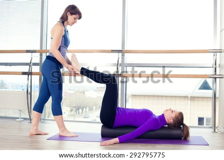 Aerobics Pilates personal trainer helping women group in a gym class - stock photo
