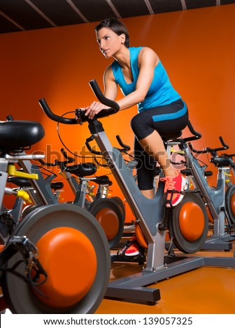 Aerobics spinning woman exercise workout at orange bikes gym - stock photo