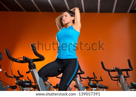 Aerobics spinning woman stretching exercises after workout at gym - stock photo