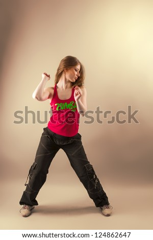 Aerobics/ zumba fitness woman dancing in studio. Active, energetic, joyful aerobic instructor in motion