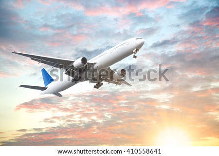 Aeroplane flying in sunset sky with beautiful cloud - stock photo