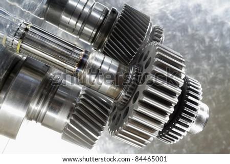 aerospace gear wheels set against brushed aluminum, blue toning concept - stock photo