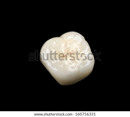 Aesthetic ceramic crown isolated on black background - stock photo