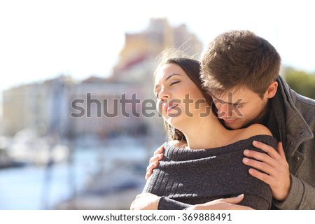 Affectionate and passionate elegant couple seducing and flirting with passion with a coast urban background in winter - stock photo