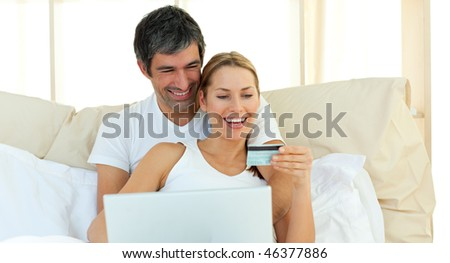 Affectionate couple buying on internet lying in the bed