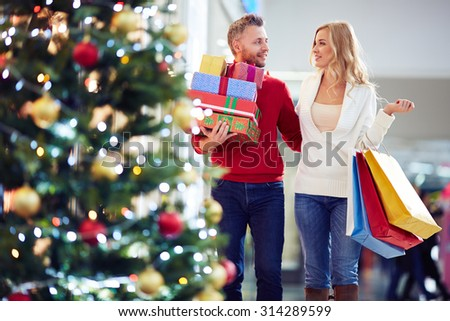 Affectionate couple carrying Christmas presents while shopping in the mall - stock photo