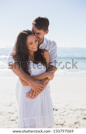 Affectionate couple cuddling at the beach - stock photo