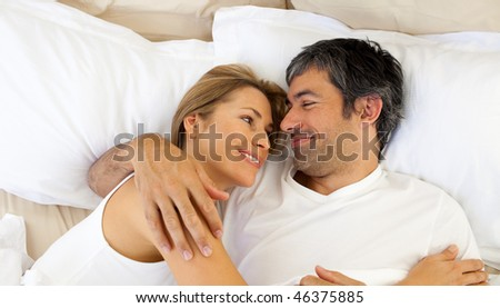 Affectionate couple hugging lying in bed at home - stock photo