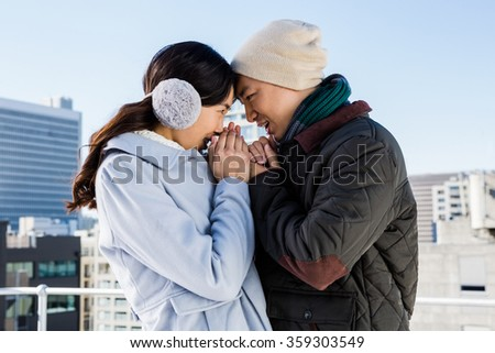 Affectionate couple in winter clothing head to head against sky