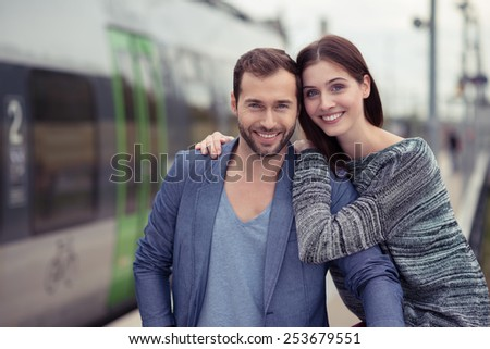 Affectionate couple posing arm in arm outdoors in an urban environment smiling happily at the camera - stock photo