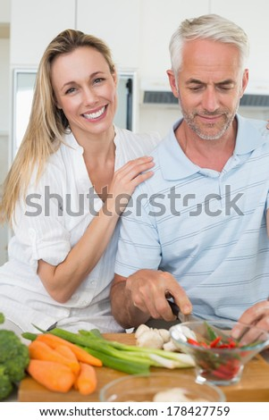 Affectionate couple preparing dinner together at home in the kitchen - stock photo