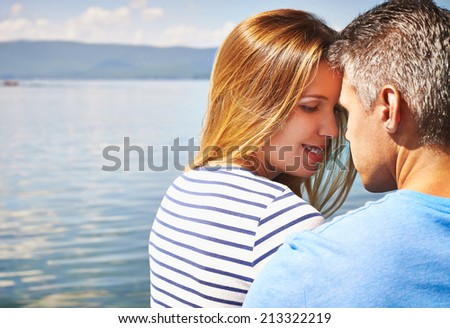 Affectionate couple spending vacation at lake - stock photo