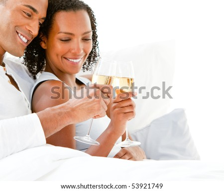 Affectionate couple toasting with Champagne lying on their bed at home