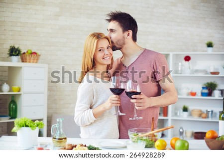 Affectionate couple with red wine standing by table with vegetarian food in the kitchen